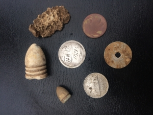 Pictured with other finds in yard, including a soldier chewed bullet from the hospital used after the battle.